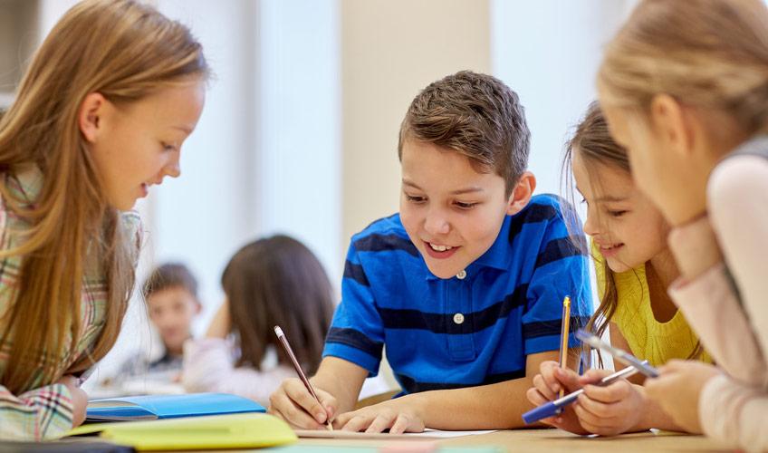 Schülerinnen und Schüler beim Schreiben und Sprechen
